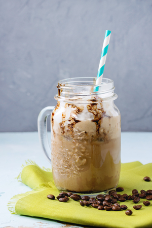 Glass mason jar with ice coffee with whipped cream, ice cream and chocolate sauce, served with coffee beans and ice cubes on green textile napkin over light blue textured background.