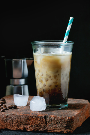 Glass of ice coffee with cream and milk, served with coffee beans, ice cubes and coffee pot on stone board over black textured background. Rustic style. Natural day light