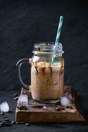 cold background: Glass mason jar of ice coffee with ice cream and chocolate sauce, served with coffee beans and ice cubes on wooden chopping board over black textured background. Stock Photo