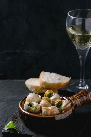alcochol: Escargots de Bourgogne - Snails with herbs butter, gourmet dish, in traditional ceramic pan with parsley, bread and glass of white wine on wooden chopping board over black textured background.