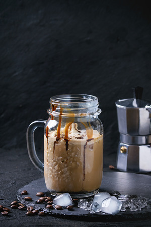 cold background: Glass mason jar of ice coffee with ice cream and chocolate sauce, served with coffee beans and ice cubes on slate stone board over black textured background.