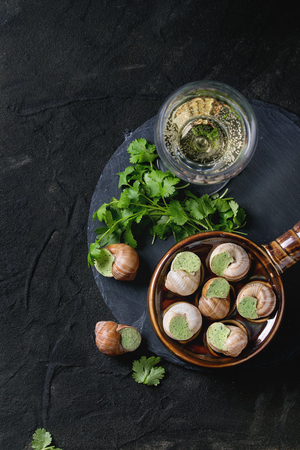 alcochol: Uncooked Escargots de Bourgogne - Snails with herbs butter, gourmet dish, in traditional ceramic pan with parsley and glass of white wine on stone slate over black textured background. Top view.