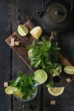 over black: Ingredients for ice green tea lime, lemon, mint, sugar, green tea and ice cubes on wooden chopping board with coctail glass and black iron teapot over old wooden background. Flat lay