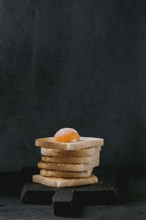 sugared: Pile of Fresh toasts bread with sugared cured yolk on black wooden cutting board over black textured background.