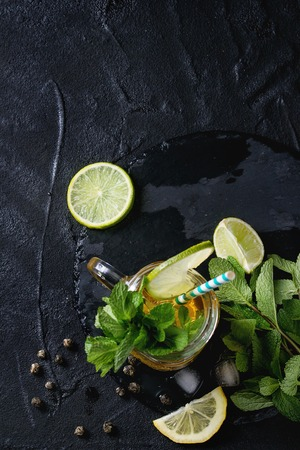 alcochol: Glass mason jar of Ice green tea with lime, lemon, mint and ice cubes on black slate stone board over black textured background. Flat lay. With copy space