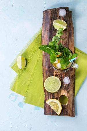 alcochol: Glass of Iced green tea with lime, lemon, mint and ice cubes on wooden chopping board over light blue textured background with green textile napkin. Flat lay