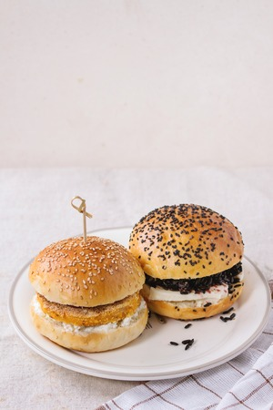 meatless: Two Homemade veggie burgers with sweet potato and black rice, served on white plate with kitchen towel over white textured background.