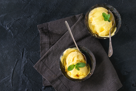 Homemade mango ice cream with fresh mint in vintage iron bowls on dark textile napkin over black textured background. Flat lay with copy space