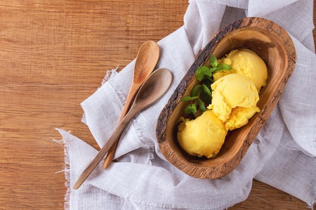 Homemade mango ice cream with fresh mint in olive wood bowl with wooden spoon, served on white textile napkin over wooden textured background. Flat lay 版權商用圖片