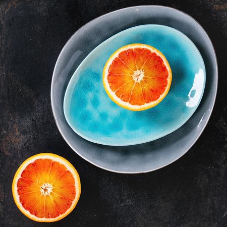 ovoid: Sliced Sicilian Blood orange fruit on bright turquoise and gray ceramic plates over black background. Flat lay. Square image