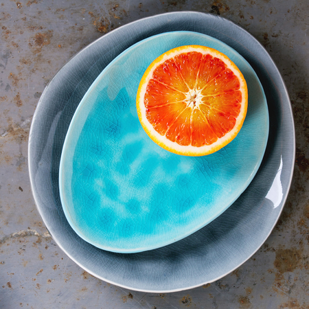 ovoid: Half of  Sicilian Blood orange fruit on bright turquoise and gray ceramic plates over rusty metal background. Flat lay. Square image