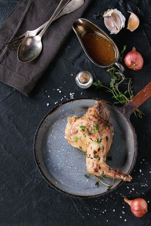 textil: Old pan with roasted rabbit leg with herbs, served with vintage cutlery on textil napkin, sauce, onion, salt and thyme over black textured background. Flat lay. With copy space