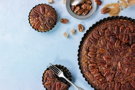 Homemade Big round caramel pecan pie and small tartlets in black iron forms, served with brown sugar, caramel sauce and vintage cutlery over blue textured background. Flat lay with copy space 版權商用圖片