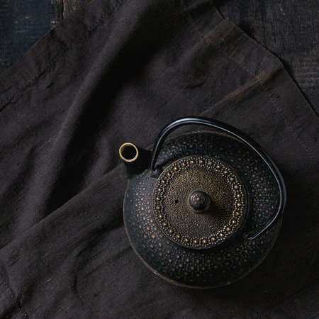 japanese people: Black iron asian style teapot on black textile napkin over old wooden table. Top view. Square image