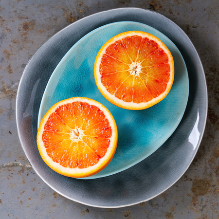 ovoid: Sliced Sicilian Blood orange fruit on bright turquoise and gray ceramic plates over rusty metal background. Flat lay. Square image Stock Photo