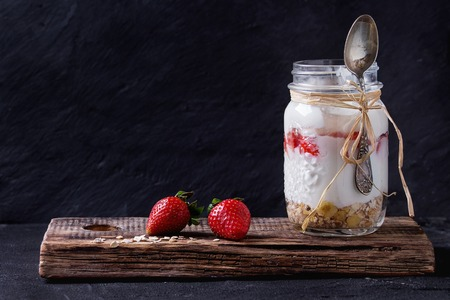 Healthy breakfast muesli, strawberries and yogurt in glass mason jar with spoon. Yoghurt served on wooden chopping board with black textured wall at background. Dark rustic style.