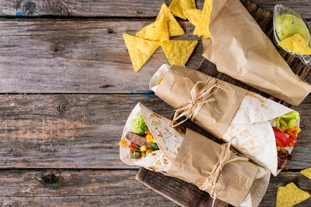 wraps: cena estilo mexicano. Dos empapeladas tortillas con carne y verduras servido con patatas fritas y nachos salsa de guacamole sobre fondo de madera vieja. aplanada