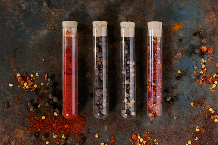 testtube: Spicy background with assortment of different hot chili and allspice peppers in glass test-tube with cork over old rusty iron background. Top view.
