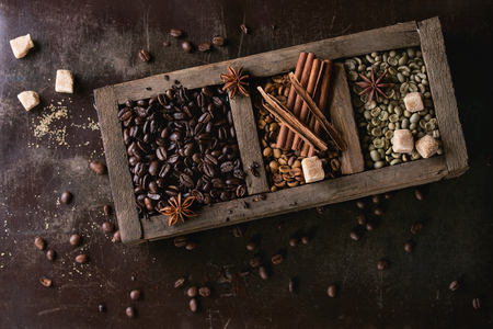 decaf: Green and brown decaf unroasted and black roasted coffee beans with spices and sugar cubes in old wooden box over dark brown textured background. Top view