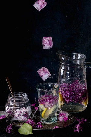falling cubes: Ice cubes with flowers falling into glass of lilac lemonade with lemon. Glass jar of sugared lilac flowers and glass pitcher on black tablecloth over black. Dark rustic atmosphere. See series.