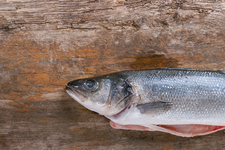 whitefish: Raw uncooked seebass fish with dry herbs over old wooden background. Top view. With copy space