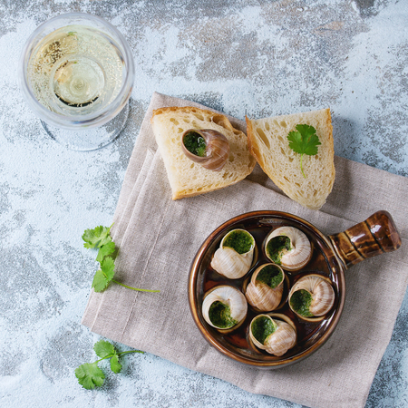 alcochol: Escargots de Bourgogne - Snails with herbs butter, in traditional ceramic pan with parsley, bread and glass of white wine on textile napkin over blue textured background. Top view. Square image
