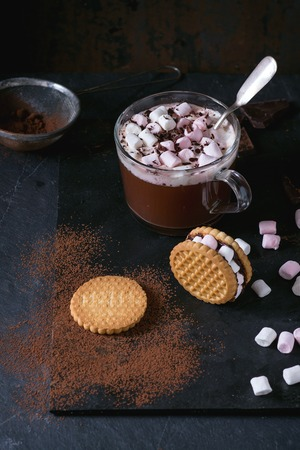 warm things: Glass cup of Hot chocolate with marshmallows, cookies stuffed by marshmallows, chopping chocolate and cocoa powder from sieve over double black slate surface. Dark rustic style. Stock Photo