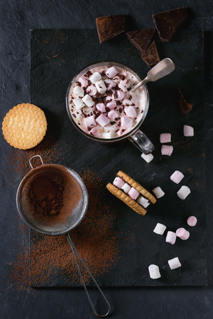warm things: Glass cup of Hot chocolate with marshmallows, cookies stuffed by marshmallows, chopping chocolate and cocoa powder from sieve over double black slate surface. Top view
