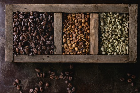 decaf: Green and brown decaf unroasted and black roasted coffee beans in old wooden box over dark brown textured background. Top view