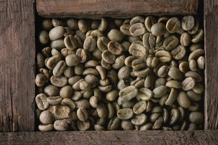 unroasted: Food background with Green unroasted coffee beans in old wooden box. Top view. Close up