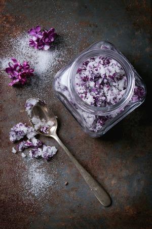 Glasgefäß mit lila Blumen in Zucker withfresh Blumen und Weinleselöffel über altem rostigem Eisenhintergrund. Draufsicht