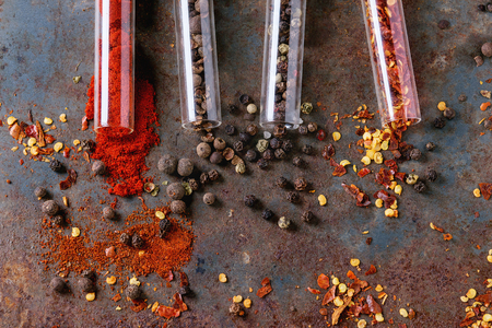 pepper flakes: Spicy background with assortment of different hot chili and allspice peppers in glass test-tube over old rusty iron background. Top view.