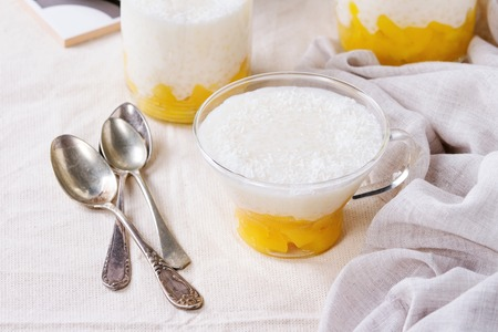 Healthy tapioca pearls pudding dessert with coconut milk and mango. Served in glass over white linen tablecloth. Close up