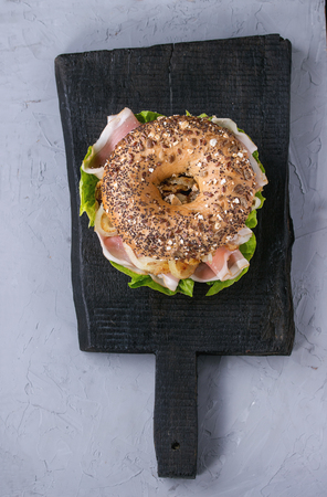 sprinkle seeds Whole Grain bagel with fried onion, green salad and prosciutto ham on black wood choping board over gray textured background. Top view