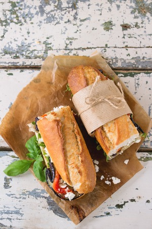 two and a half: Two half of vegetarian baguette submarine sandwich with grilled eggplant, pepper and feta cheese served on baking paper over old white wooden background. Top view Stock Photo