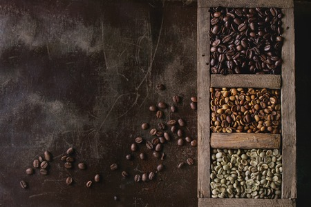 decaf: Green and brown decaf unroasted and black roasted coffee beans in old wooden box over dark brown textured background. Top view. With copy space