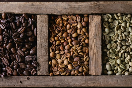 decaf: Food background with green and brown decaf unroasted and black roasted coffee beans in old wooden box. Top view. Close up Stock Photo