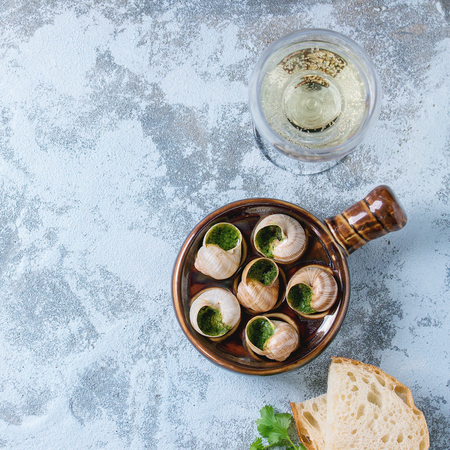 alcochol: Escargots de Bourgogne - Snails with herbs butter, in traditional ceramic pan with parsley, bread and glass of white wine over blue textured background. Top view, copy space. Square image