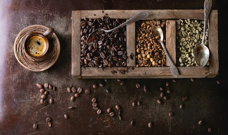 decaf: Green and brown decaf unroasted and black roasted coffee beans in old wooden box, and ceramic cup of fresh making coffee over dark brown textured background. Banner top view Stock Photo