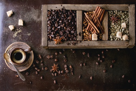 decaf: Green and brown decaf unroasted and black roasted coffee beans with spices and sugar in old wooden box, and ceramic cup of fresh making coffee over dark brown textured background. Top view Stock Photo