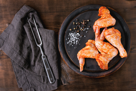 raw food: Raw Marinated chicken meat wings and legs for BBQ, served on round wood chopping board with seasoning and vintage meat fork on textile over dark wooden background. Top view with copy space. Stock Photo