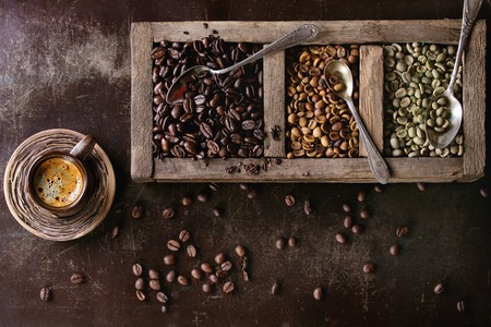 variation: Green and brown decaf unroasted and black roasted coffee beans in old wooden box, and ceramic cup of fresh making coffee over dark brown textured background. Top view