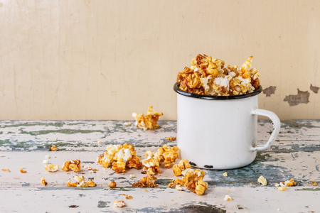 enameled: Prepared caramelized sweet popcorn served in vintage white enameled mug over old white wooden background. With space for text.