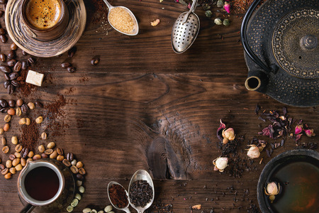 Food background tea and coffee theme. Different black and green dry tea, different coffee beans, cup of hot tea and coffee,  teapot over dark wooden background. Top view. Space for text Stockfoto