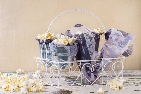 buttered: Prepared salted and buttered popcorn served in small buckets with paper inside and cornets in white decorative stand over old white wooden background. With space for text