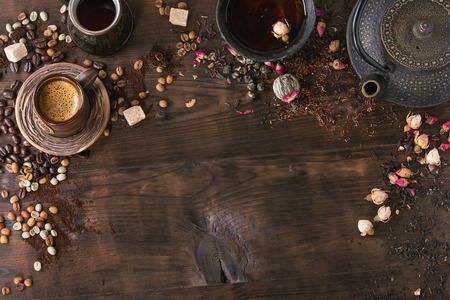 Food background tea and coffee theme. Different black and green dry tea, different coffee beans, cup of hot tea and coffee,  teapot over dark wooden background. Top view. Space for text 스톡 콘텐츠