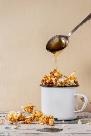 enameled: Prepared caramelized sweet popcorn served in vintage white enameled mug over old white wooden background. Caramel sause is poured from spoon. With space for text.