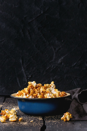 enameled: Caramelized sweet popcorn served in vintage enameled bowl with brown sugar and textile napkin over dark wooden background.