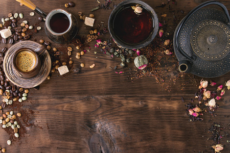 Food background tea and coffee theme. Different black and green dry tea, different coffee beans, cup of hot tea and coffee,  teapot over dark wooden background. Top view. Space for text Stock Photo