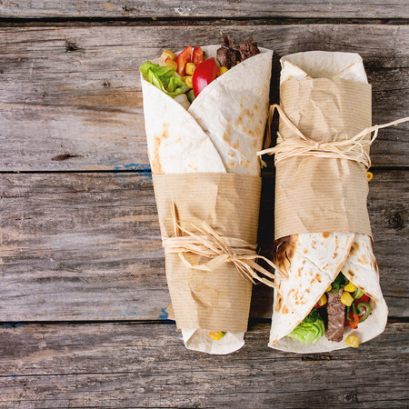 Mexican style dinner. Two papered tortillas with beef and vegetables over old wooden background. Flat lay. With copy space. Square image Foto de archivo